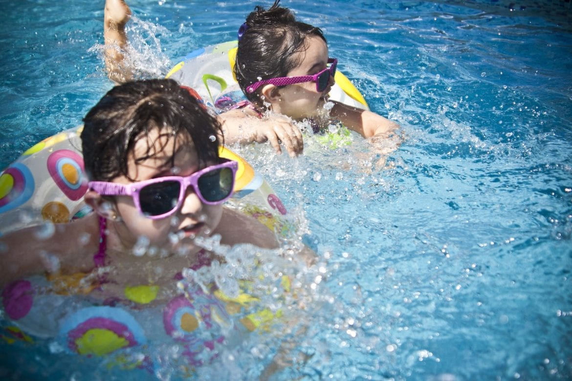 Children wearing sunglasses and swimming in a pool